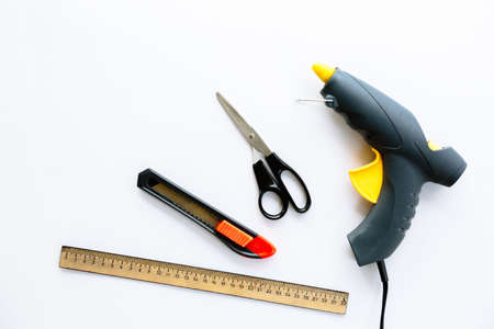Ruler, knife, scissors and glue gun isolated on a white background. Necessary tools for creating creative crafts. Stationery that can be used by adults or under their supervision. Top view layout.