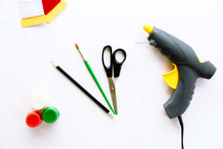 Scissors, pencil, brush, paints, gouache, acrylic, thread and glue gun isolated on a white background. Stationery tools necessary to create a creative craft. Top view layout.