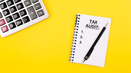 Tax audit written as a list into the notepad. Accountant or auditor desktop layout with calculator and note with important day reminder. Positive yellow background as a symbol of honest taxes.