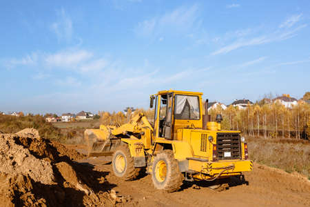 large yellow wheel loader aligns a piece of land for a new building. Preparation of the land for the auction. Leveling the landscape and adding sand for construction. Banner wallpaper.