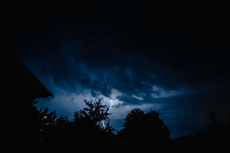 Multiple lightening bolts flash through a dark dramatic sky. A terrible destructive natural phenomenon. The view from the house. Weather forecast.