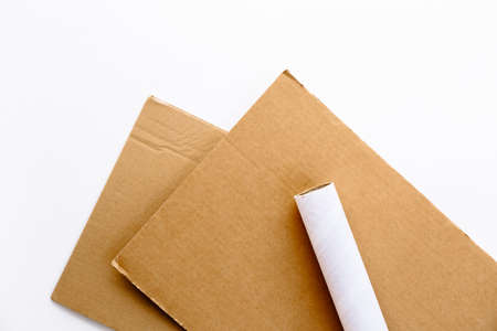 A pair of sheets of brown cardboard and a white tube from a paper towel on a white background. Material for use in a step by step instruction for the manufacture of New Year's crafts, Christmas tree. Фото со стока