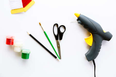 Scissors, pencil, brush, paints, gouache, acrylic, thread and glue gun isolated on a white background. Stationery tools necessary to create a creative craft. Top view layout. Standard-Bild