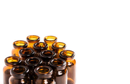 Many empty brown glass medical bottles isolated on a white background. The course of treatment is completed. Mass vaccination. Capacities for tablets. Close-up. Production of containers.