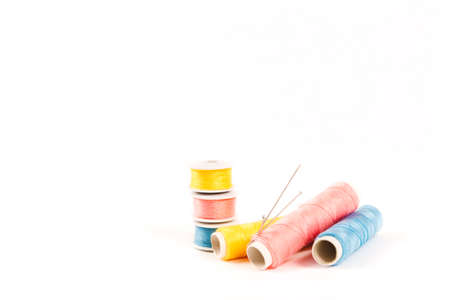 Three spools and bobbins of thread of yellow, blue and pink color with needles on a white background in a minimalistic style with a place for text. Items for needlework, embroidery and sewing. Studio shot, side view.