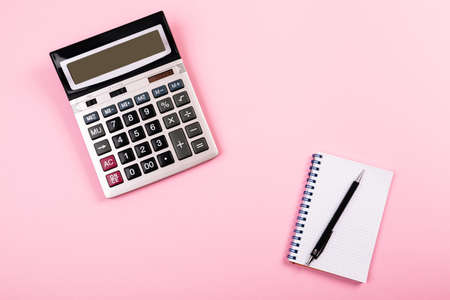 Large silver calculator with black pen and white paper notebook laying on a pink background. Concept of finance, business, calculations, education, school, math, accounting, computing, profit, tax. Фото со стока