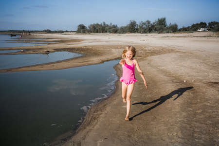 A little seven-year-old girl in a pink swimsuit runs along the lake in a good cheerful mood with a smile on her face. Summer lifestyle the holidays. Health tempering with water procedures and walks.