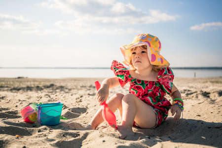A little cute girl of three years old in a red dress and a panama hat sits on the beach and plays in the sand with plastic toys: a bucket, molds and a shovel. Summertime trip. Family holiday. Close-up
