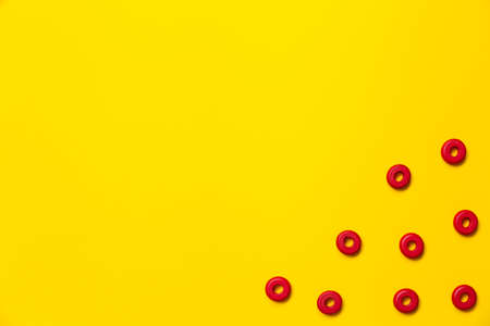 On a yellow background, there are rings of red color of the same size, which form a frame on children's education and development. Backdrop for placing text and other information.