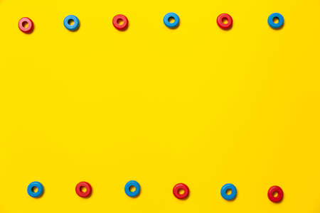 On a yellow background, there are rings of red and blue colors of the same size, which form a frame on children's education and development. Backdrop for placing text and other information.