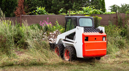 A skid steer loader clears the site for construction. Land work by the territory improvement. Machine for work in confined areas. Small tractor with a bucket for moving soil, turf and bulk materials. Foto de archivo