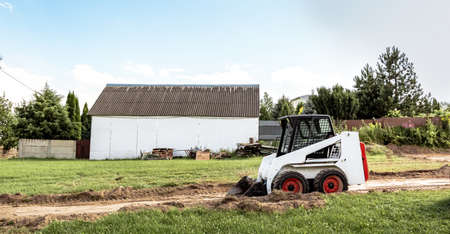 A skid steer loader clears the site for construction. Land work by the territory improvement. Machine for work in confined areas. Small tractor with a bucket for moving soil, turf and bulk materials.