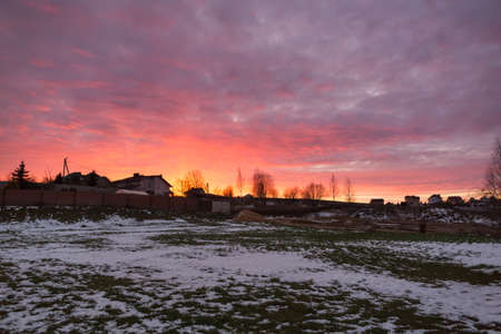a flat piece of land put up for sale at auction in winter with a beautiful pink cloudy sunset Stock Photo