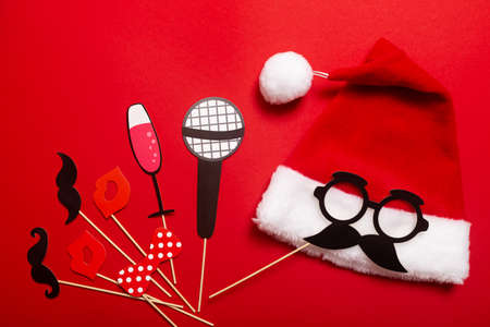 A red color banner with a Santa hat with a white pompom and a face from glasses and mustache. A props for entertaining guests at a New Year corporate festive or a karaoke party for a team of barbers.
