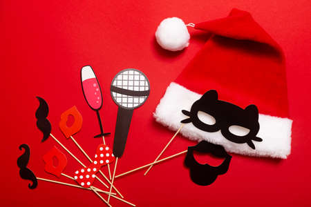A red color banner with a Santa hat with a white pompom and a face from cat mask and mustache. A props for entertaining guests at a New Year corporate festive or a karaoke party for a team of barbers.