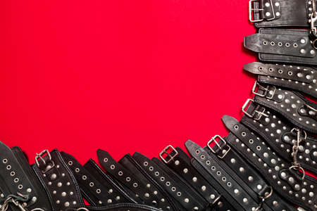 Red color banner with black leather bracers and metal rivets for shackling hands or legs and performing games. BDSM subject. Background for advertising adult products and toy store.