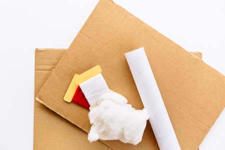 A sheets of brown cardboard, tube of paper towel, threads and wadding on a white background. Material for use in a step by step instruction for the manufacture of New Year's crafts, Christmas tree.