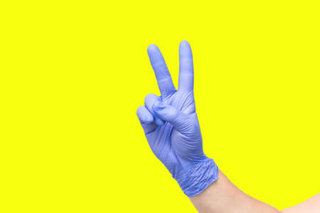 male hand on yellow background showing the symbol of victory or number two or sexual insult