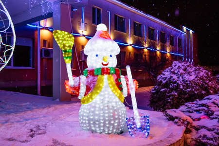 A snowman from a glowing garland at a New Year's fair on a winter evening. Christmas bright decor illuminations. The holiday happy mood. Imagens