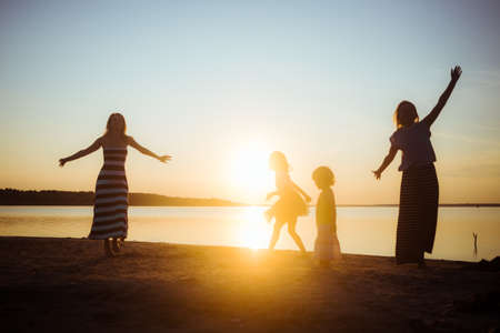 Silhouettes of children and their mothers jumping and having fun on the beach in sunset light. Good mood and pastime among the younger and older generation. Beautiful landscape.