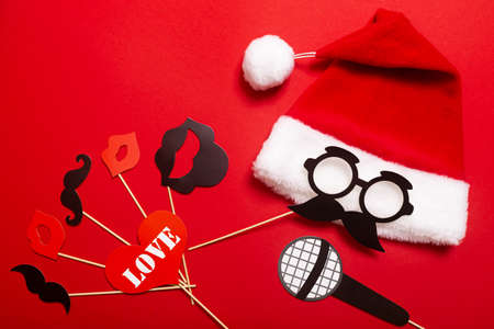 Red banner with a Santa hat with a white pompom and a face from glasses and mustache. A props for entertaining guests at a New Year corporate festive, speed dating or a karaoke party.