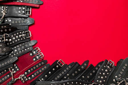 Red color banner with black leather bracers and metal rivets for shackling hands or legs and performing sexual games. BDSM subject. Background for advertising adult products and sex toy store.