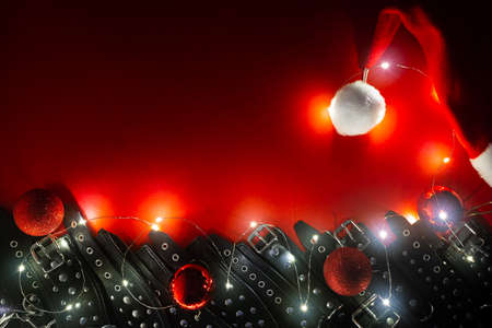 New year banner with Santa hat, garland, christmas balls and black leather bracers and metal rivets for shackling hands or legs. BDSM entertainment. Background for adult toys or sex shop.