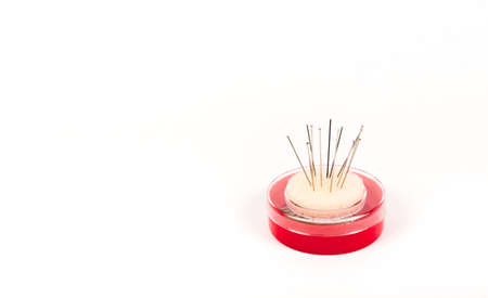 Red pack of tailor pins. Needle storage box with foam rubber pincushion. Sewing tool banner isolated on white background with copy space. 免版税图像