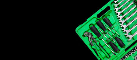 Green set of construction tools: wrenches, adjustable pliers, screwdriver and so on on a black background. Banner with place for text for a hardware store or professional repair or DIY.