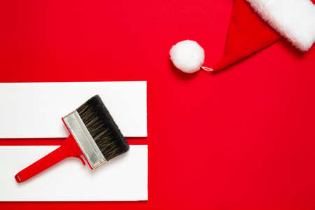 A large new red plastic paint brush in metal edging for painting and two white wood planks and Santa Claus hat on a red background. Christmas banner with copy space for a hardware store or art shop.