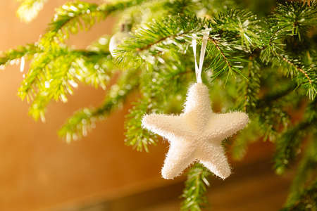 Merry Christmas and Happy New Year greeting card. White toy star made of plastic. Home decoration and giving coziness and atmosphere of celebration and magical mood. Close-up.