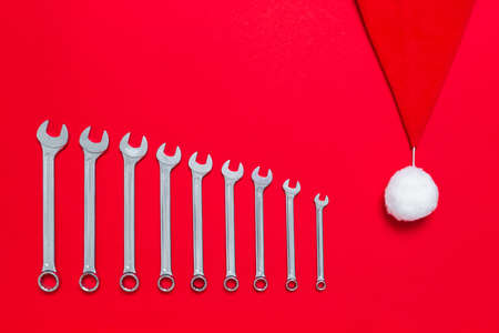 Wrenches different size decorated with santa claus hat on a red background. New Year banner with tools. Postcard with place for greeting text with industrial holiday concept. Close-up.