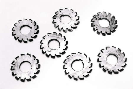 Several metal milling disc cutters for industrial equipment. The tool is isolated on a white background. Close-up.