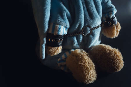 Toy bear is kneeling, facing the wall, hands behind his back in handcuffs. Child abuse. Abduction of children. Slavery and the sale of people. Psychological violence in the family, society and school. Banque d'images