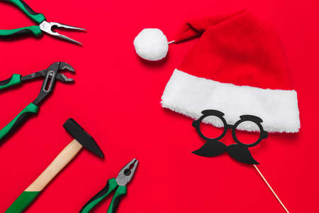 A set of quality green building tools to repair a car or a house and santa claus hat on a red background. Do it yourself instruments. Banner for a Christmas advertise construction shop with copy space
