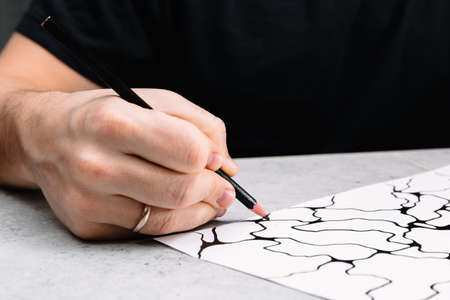 Man is drawing an abstract imaginary picture of curves by a black pencil in his hand. A psychological art therapy tests.