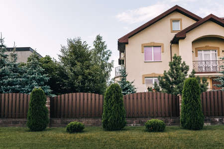 Vertical sections of brown metal profile fence. Live plantings. Green thuja, bushes and lawn. The local area decor. A house and a garden. Landscaping of the territory. Capital fencing. Vacation home.