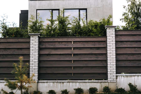 Horizontal sections of brown wooden boards fence and white brick pillars. Live plantings. Green thuja, bushes and pine. Territory landscaping. Capital fencing. Production of fence for a country house.