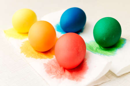 Close-up of stage of drying painted eggs after painting process in food coloring. Home decorations for the holiday. The main symbol of Easter. Bright color: yellow, orange, red, green and blue. Five.