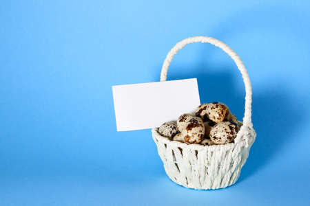 White basket with quail eggs on blue paper background with copy space or empty place for text. Easter holiday. Visiting card. Religious straw handmade decor. Springtime design. Healthy food product.