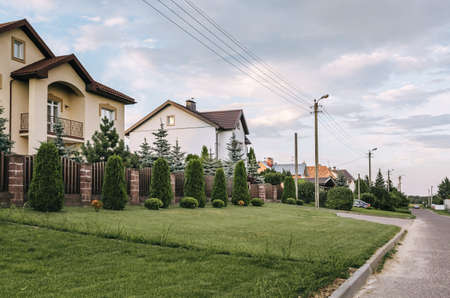 Street with private country houses. Well-groomed area with evergreens and a dense green lawn. A fence made of vertical metal profiles in brown. Tui and other trimmed bushes. Power line. Landscaping. Stockfoto