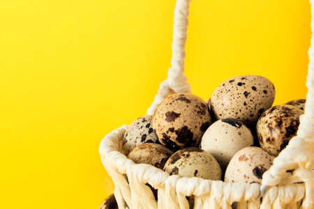 Yellow background with white straw basket full of quail eggs. Copy space. Empty text place. Mockup design of Easter holiday. Handmade decoration. Healthy food product. Summer mood color. Side view. Stockfoto
