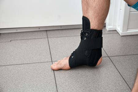 The male leg is fixed in a medical bandage. Ankle fracture or sprain. Lacing and tight fit of the foot. A healthy and diseased part of body. Post-fracture therapy and development. Treatment accesuare. Stockfoto