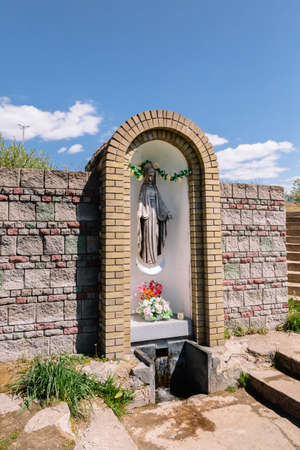 Wall with Niche in which there is a sculpture of the Holy Virgin Mary made of bronze in crown and on the moon. Nearby there is a source of holy water - spring. The main person in the Christian faith.