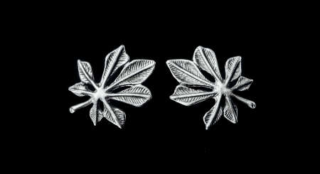 Cannabis. Two silver hemp earrings lie on a black background with a mirrored surface. Silver occult jewelry.