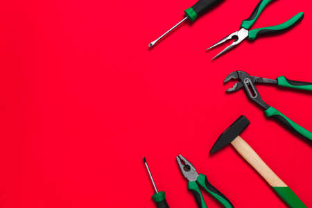 A set of quality green building tools to repair a car or a house on a red background. Do it yourself instruments. Banner for advertising construction shop with copy space. Business card.