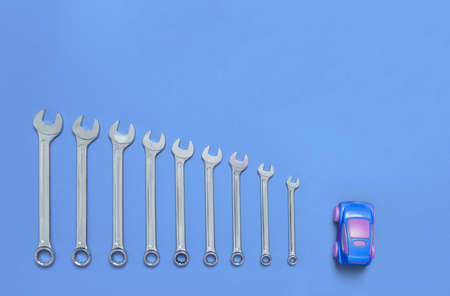 Set of wrenches different size and small toy car lays on a blue background. Banner with tools of locksmith for car service and tire fitting with industrial concept. Close-up.