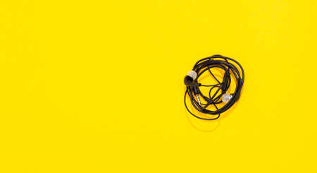 Black twisted earphones on yellow background with copy space. Tangled into a knot. Small vacuum or in-ear headphones. Banner. Empty place for text. Top view.