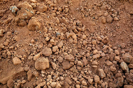 Close-up of the ground. Dry texture. Soil is a useful natural resource. Brown color or dark orange of clay. Construction sand material. Abstraction. Backdrop. Priming top view. Natural design mockup.