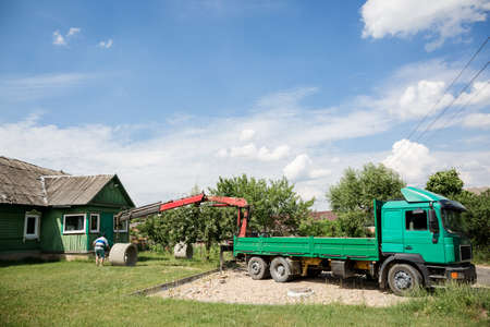 A truck with a crane manipulator unloads a concrete ring. Green lorry. Business transport cargo transportation. Delivery of bulky building material. Summer. Mobile crane.